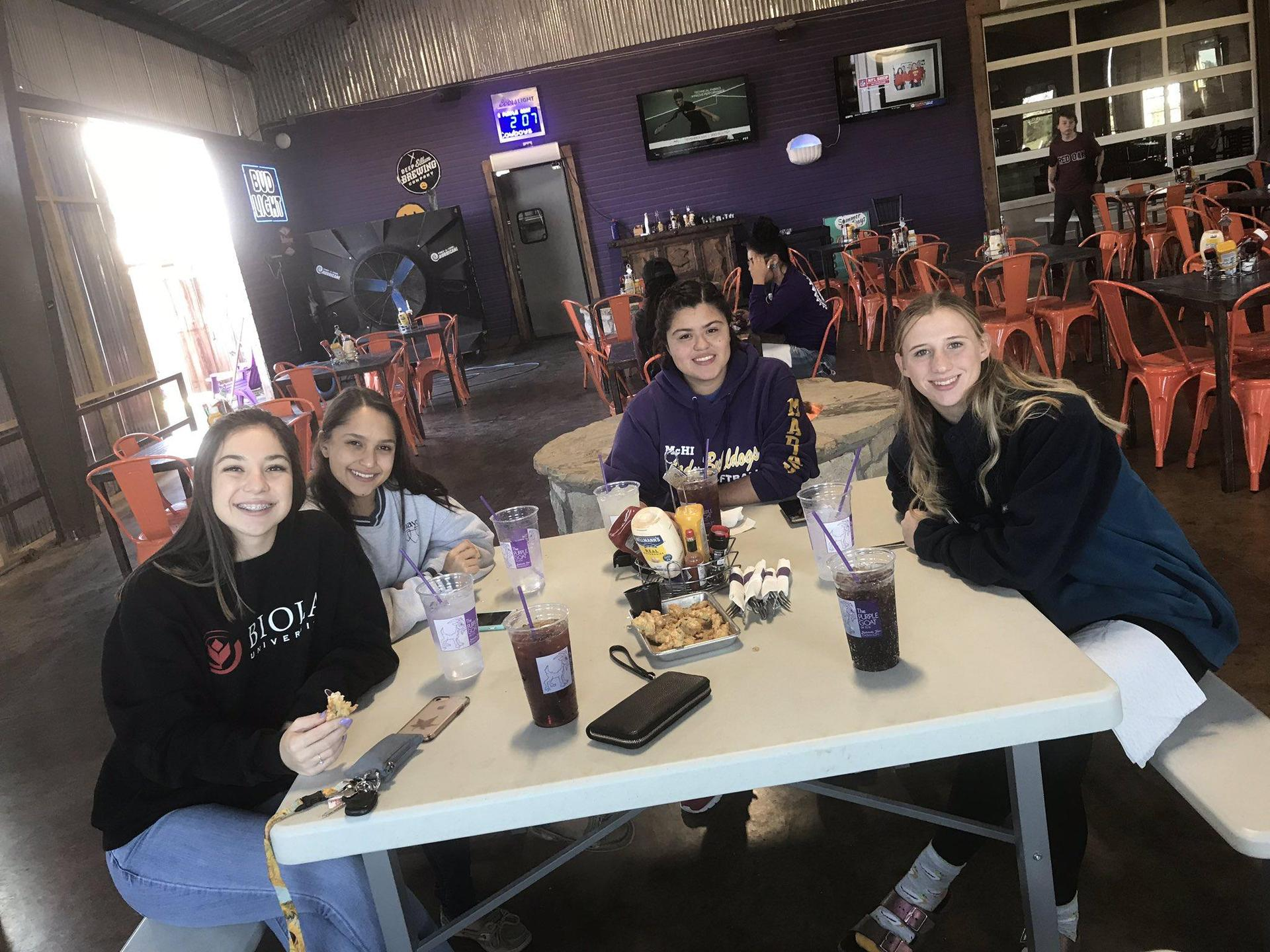 students sitting and eating in restaurant smiling
