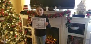 Valerie holding honor roll certificate