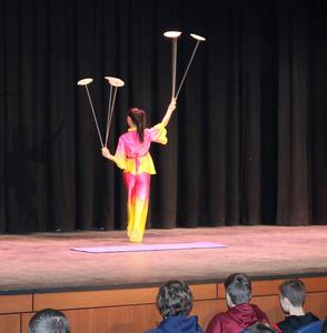 Performer in colorful costume juggles/spins plates as Dance China New York (DCNY) took Roosevelt students on a tour of the culture, customs, language and dance heritage of China during a recent assembly.