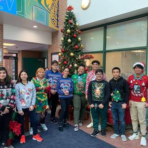 group of students wearing ugly sweaters in the front entryway by the Christmas Tree