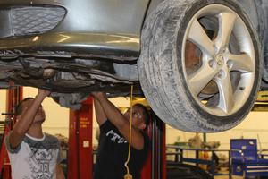 group of students working under a car for automotive class