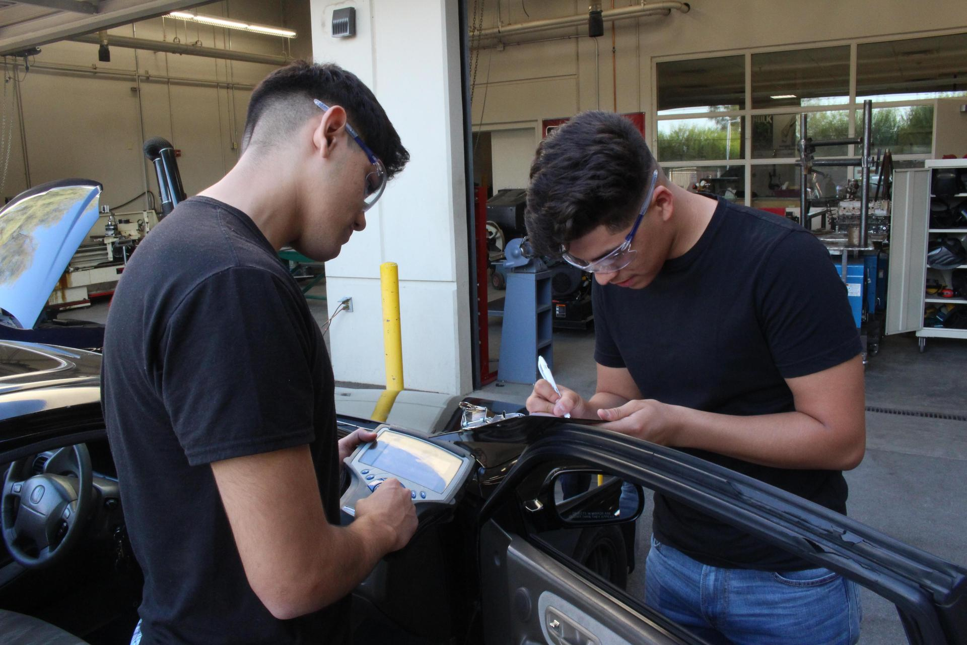 Two students working on taking measurements off a car