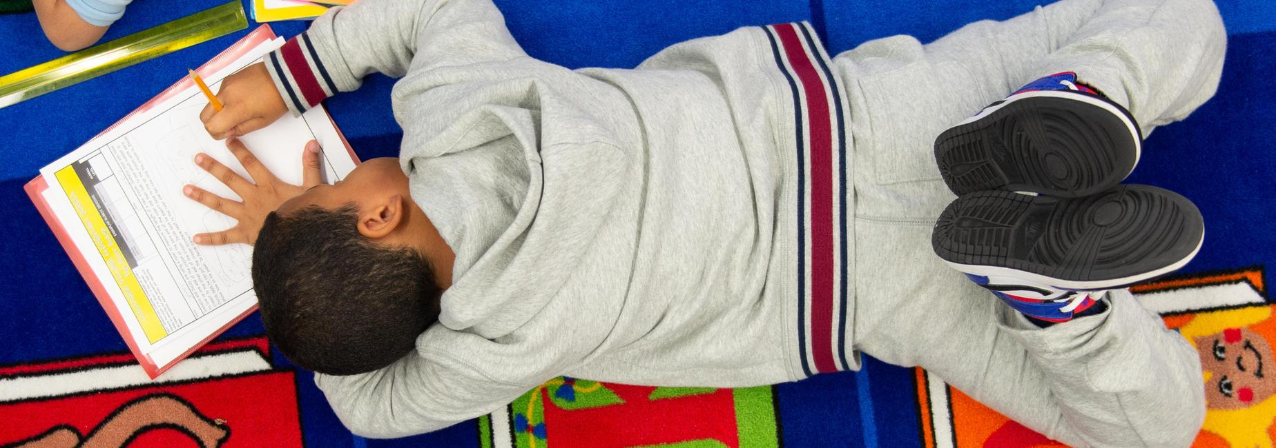 An elementary school student lying face down on a carpet writing.