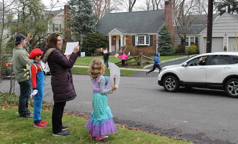 Photo of Washington family waving to teachers driving by as part of a car parade.