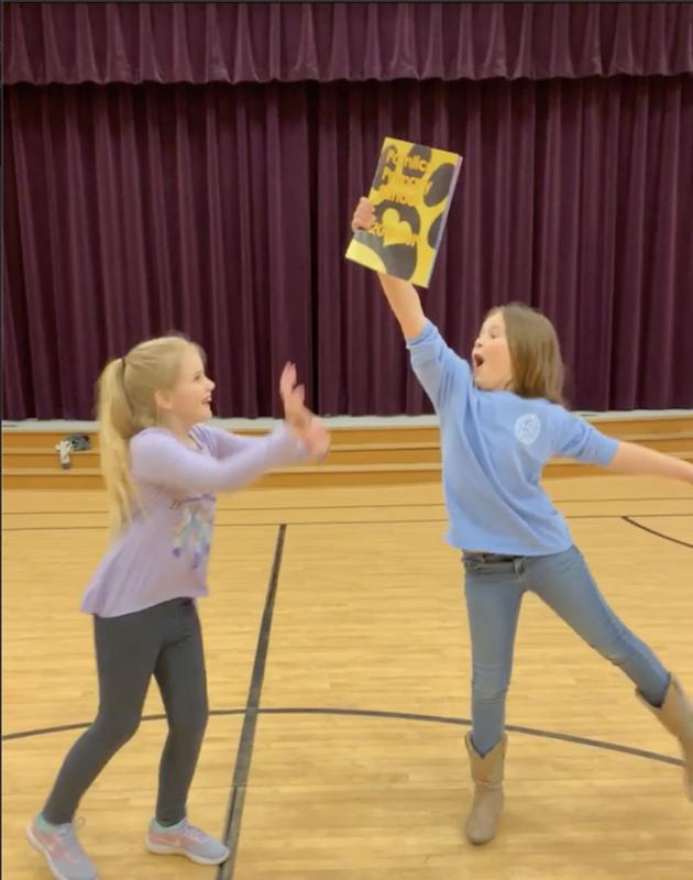 Girls holding yearbook