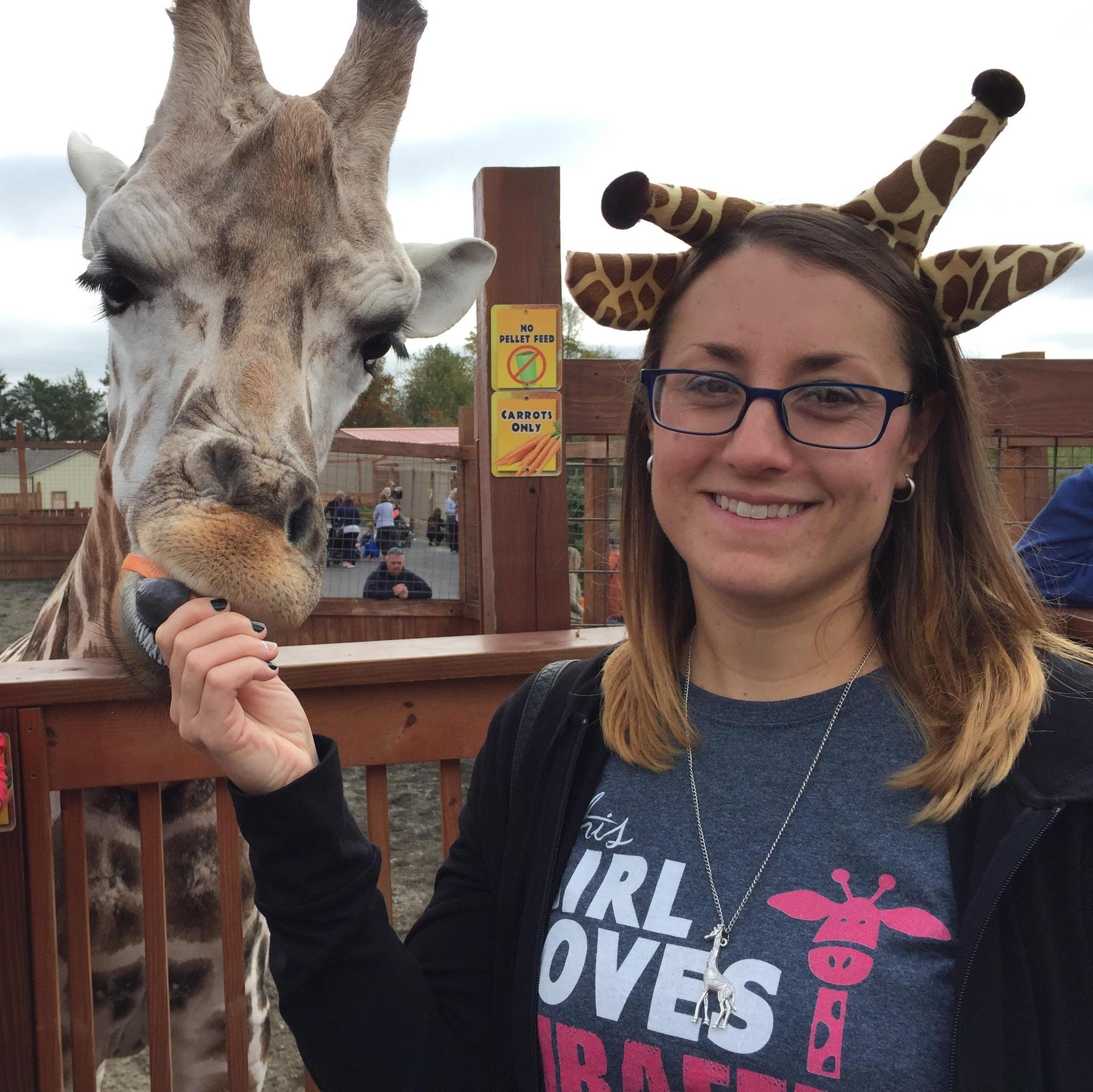 Ms. Violette feeding a giraffe