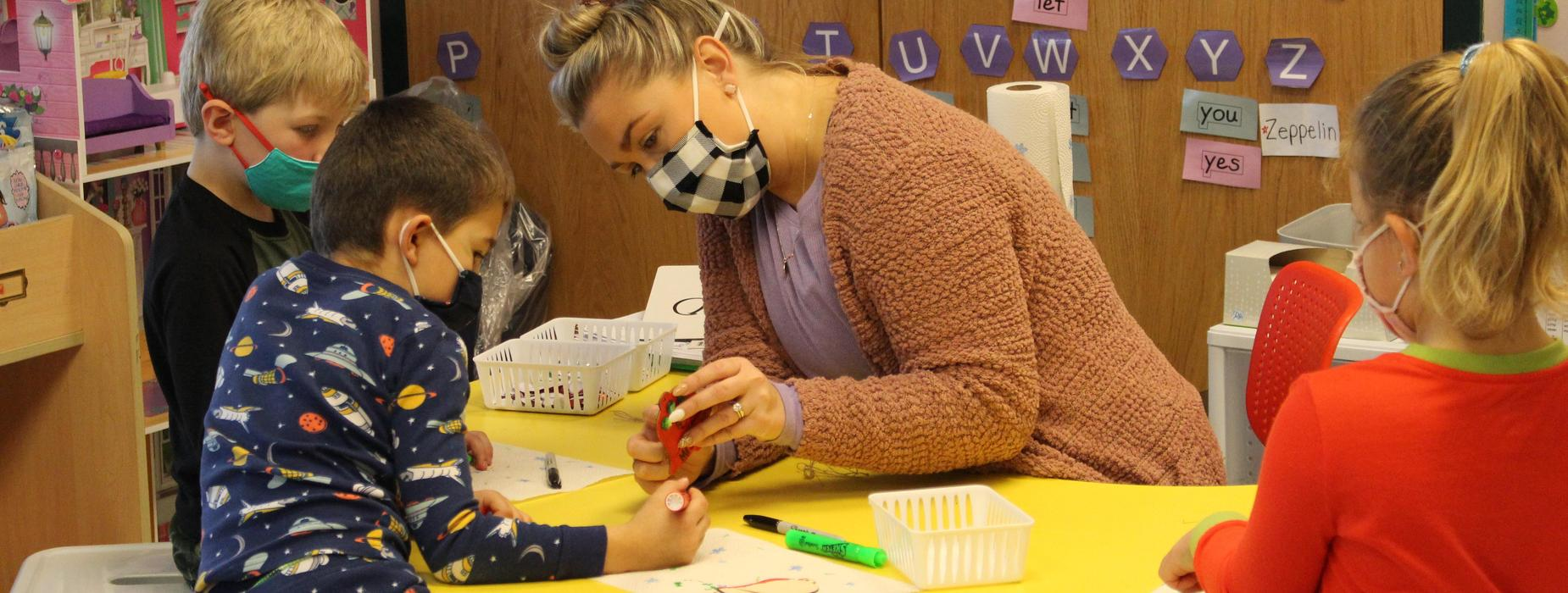 Teacher helping a students with crafts