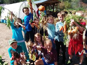 students holding up harvest carrots
