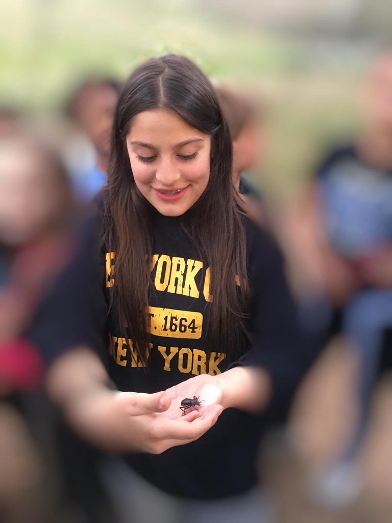 student holding bug