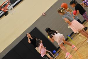 Kindergarten students playing basketball with their teacher.