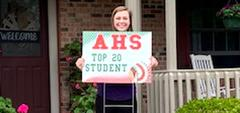 Girl in front of house with sign, 'AHS Top 20 Student'