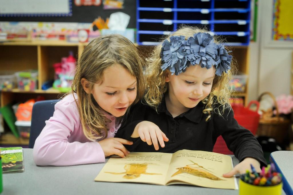 girls reading a book together