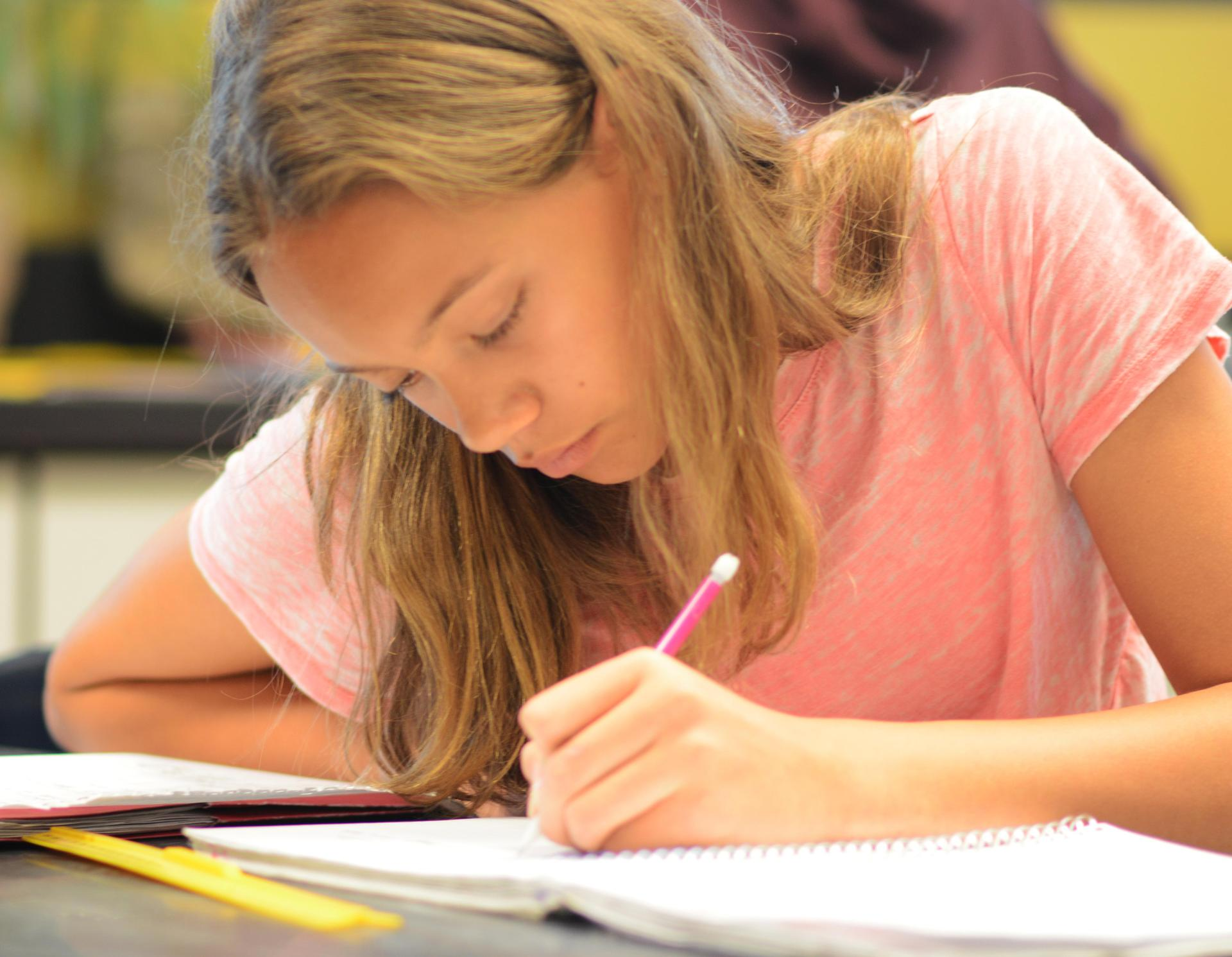 Middle school girl writing in notebook in the Center for Learning Excellence