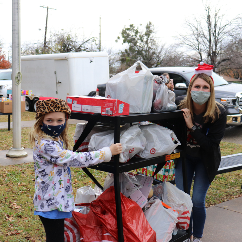 Dyer staff and student roll a cart full of donated toys into the building