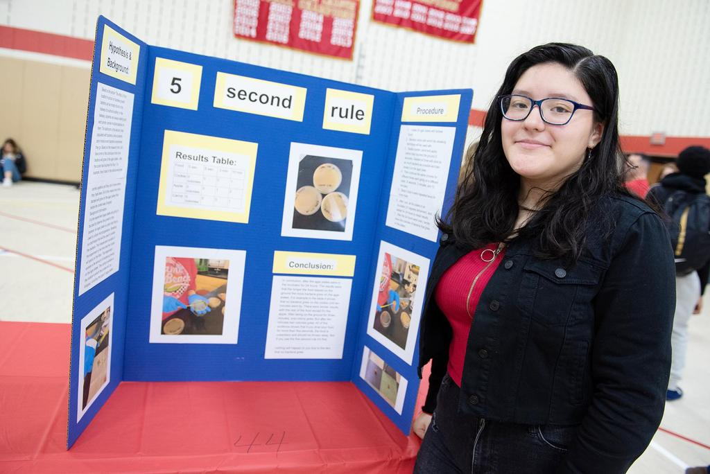 A female student in front of her project, Five Second Rule