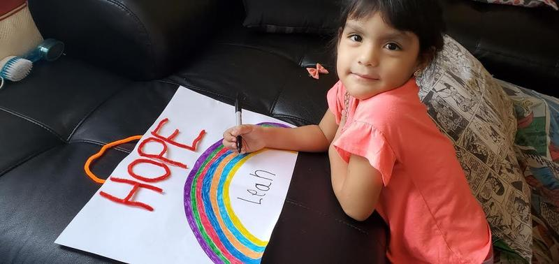 girl drawing rainbow on her sofa