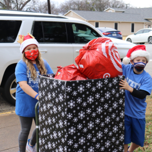 dyer students roll a box almost as tall as them that is overflowing with toys inside the school