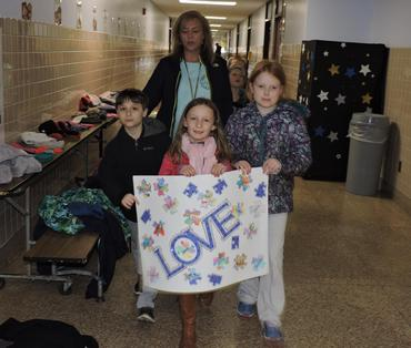 students carrying autism awareness sign with their class and teacher