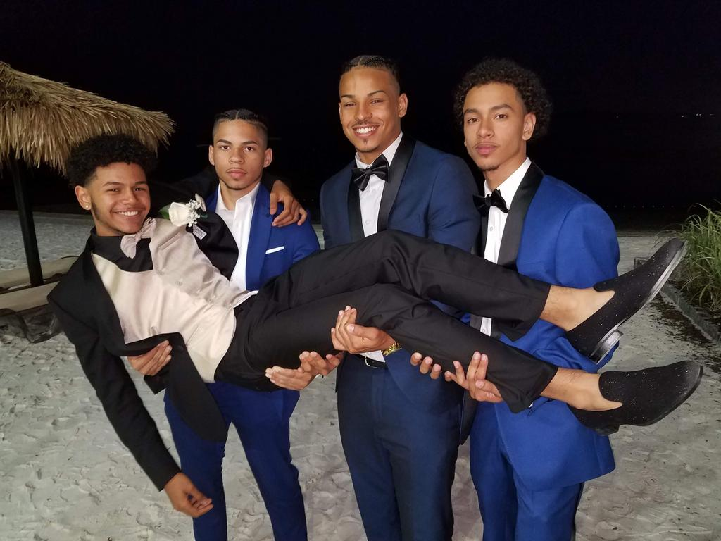 Three suited students carrying one suited student