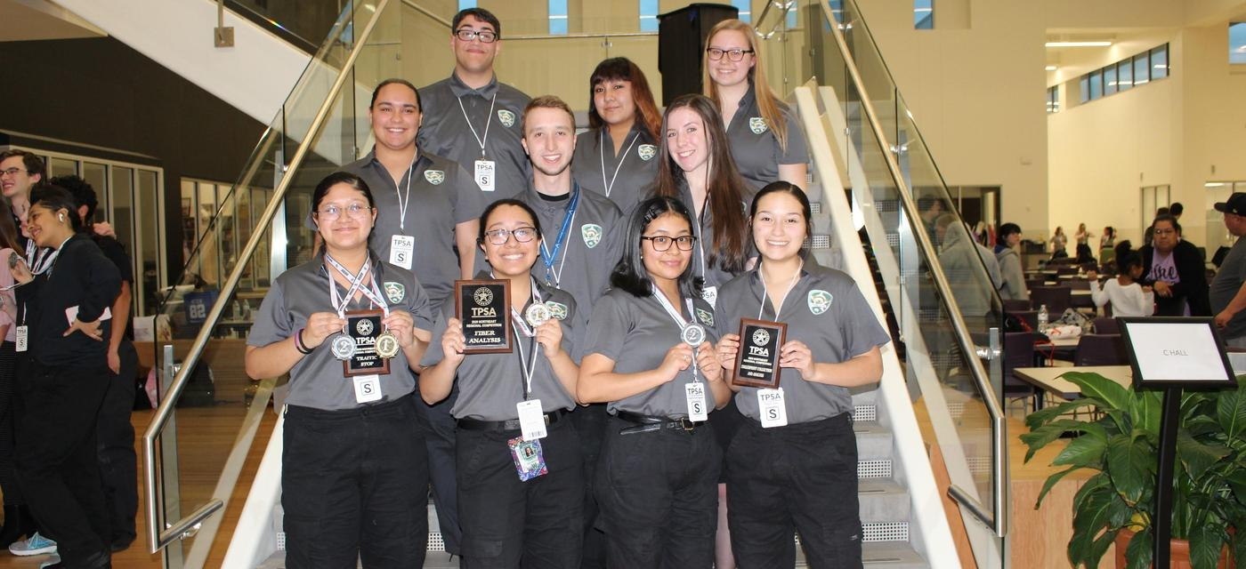 10 criminal justice students pose on stairs with awards they earned at state contest