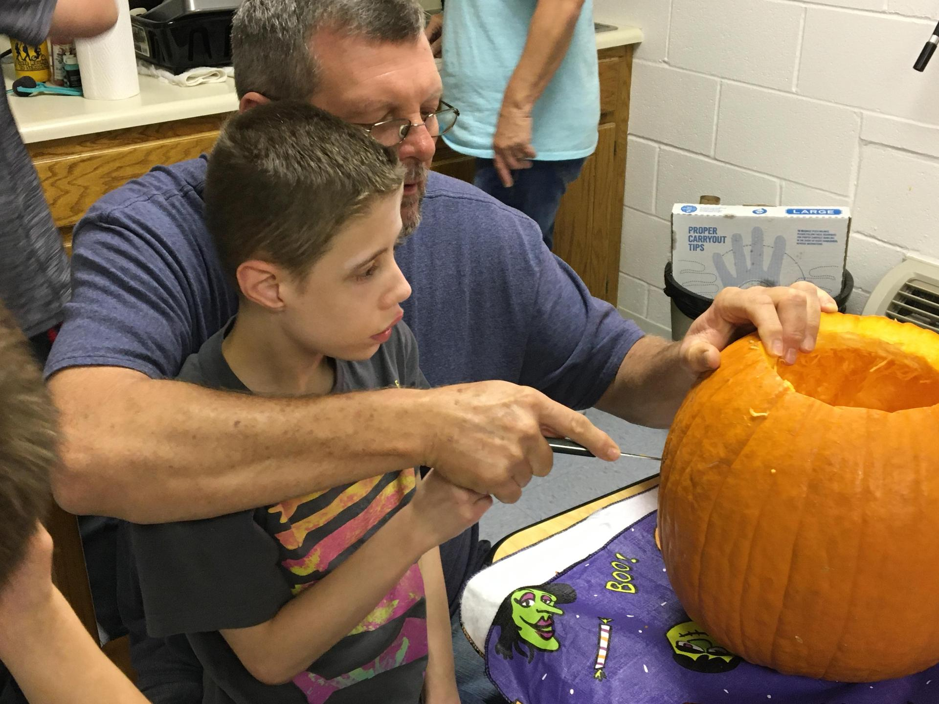 Student and RCs carving a pumpkin together while seated