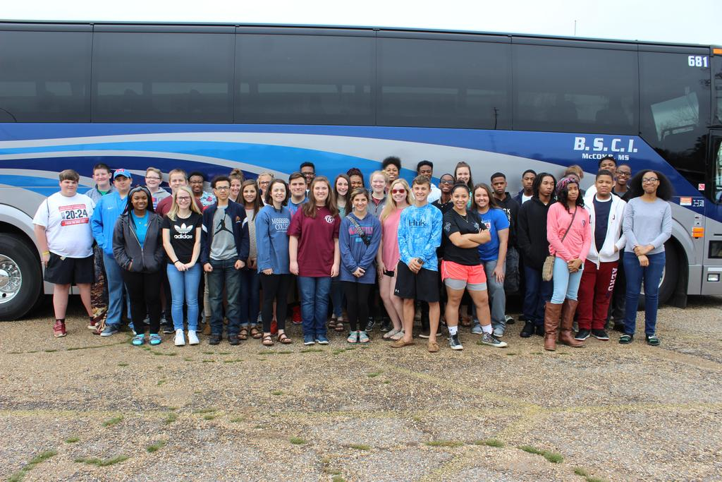 Students standing in front of a bus preparing for a field trip