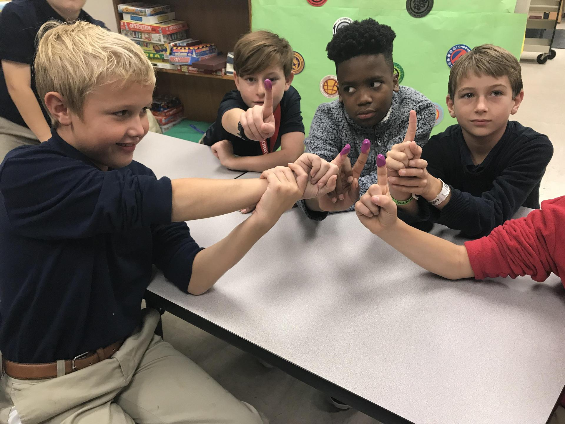 4th graders show off the proof of voting with their purple fingers on election day.