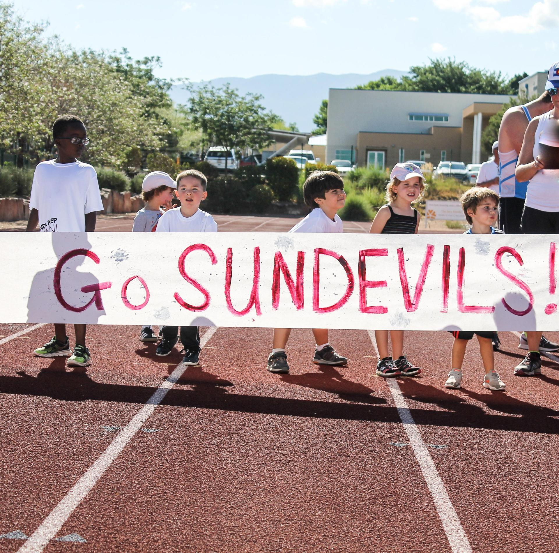 Children hold 'Go Sundevils' banner for 5K race