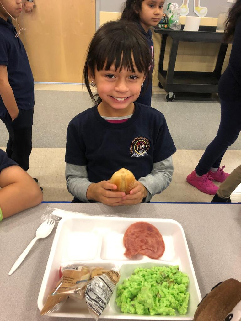 girl holding a piece of bread that came with her breakfast