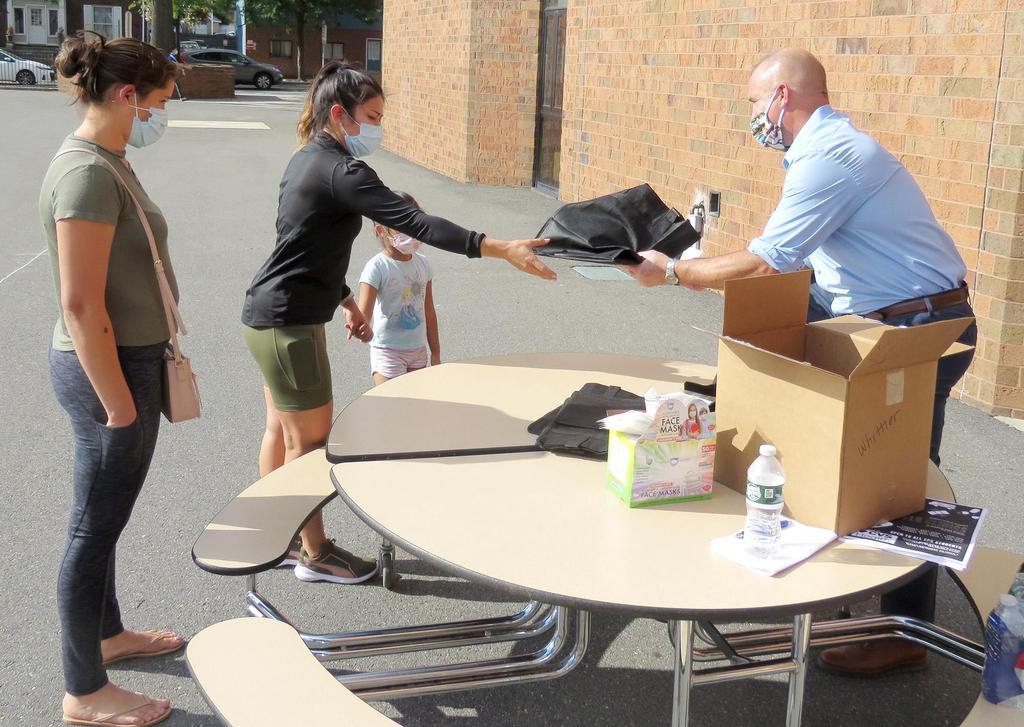 Principal McLucas hands a Chromebook to a parent