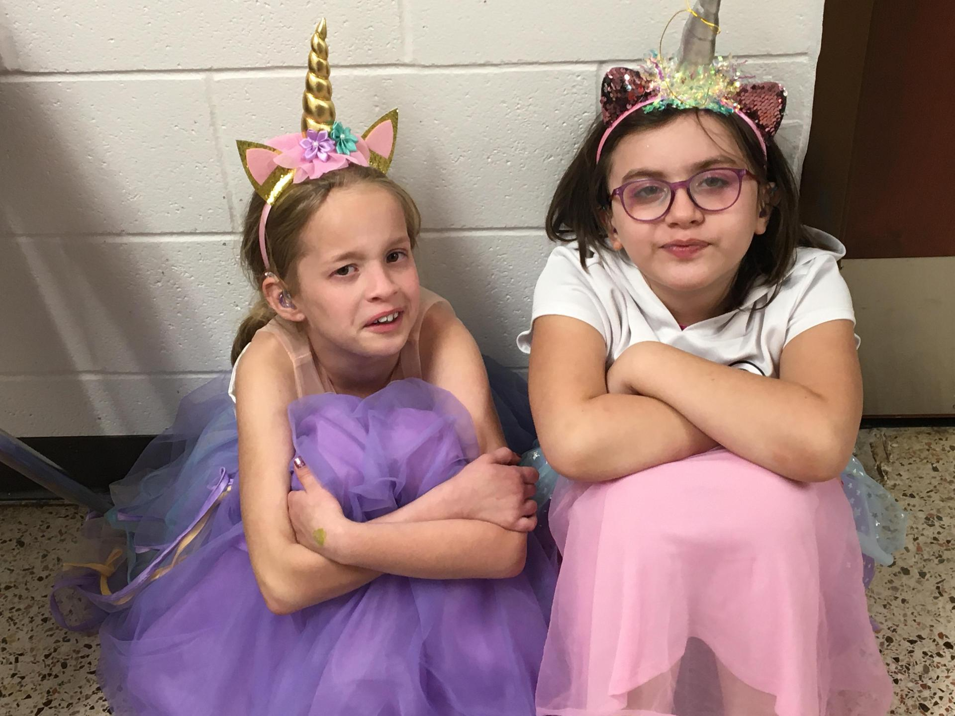 Two little girl unicorns sitting with their backs to a wall