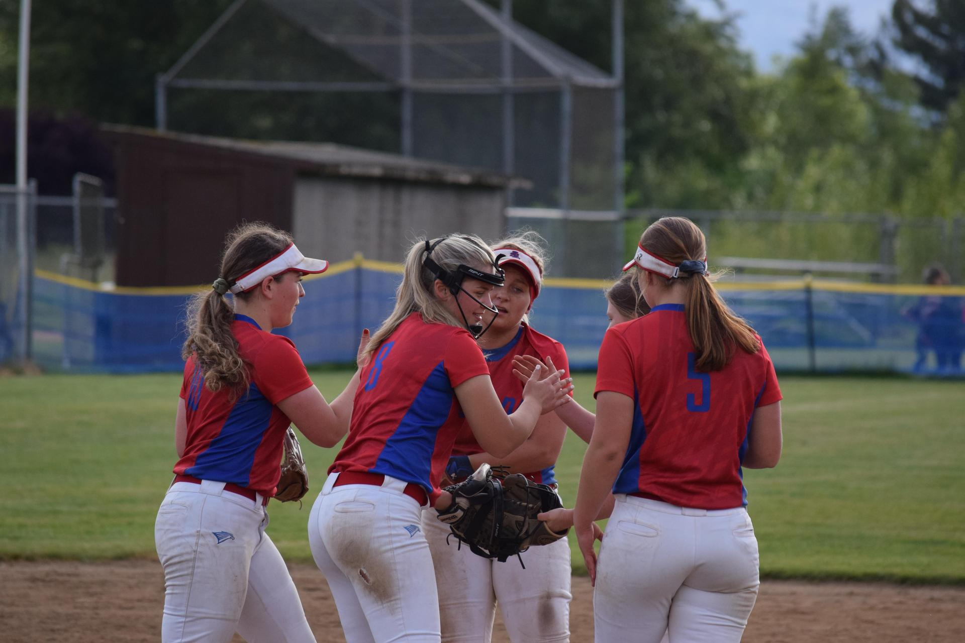 softball players meet at the mound