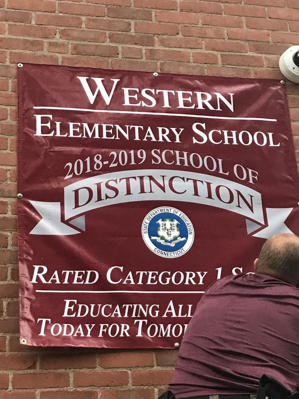 Western School of Distinction banner being hung up on building.