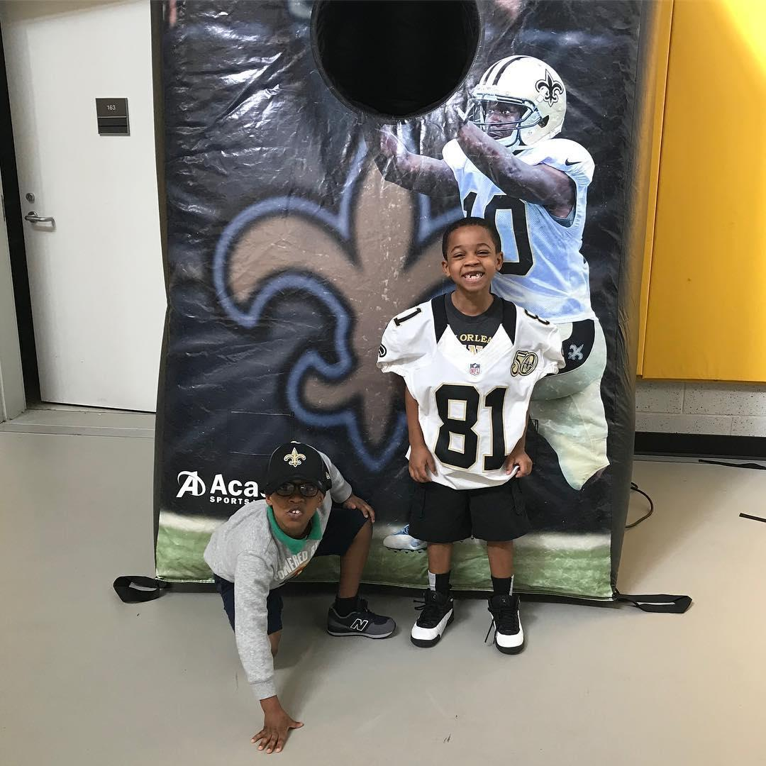 Two KECP students pose by a Saints poster