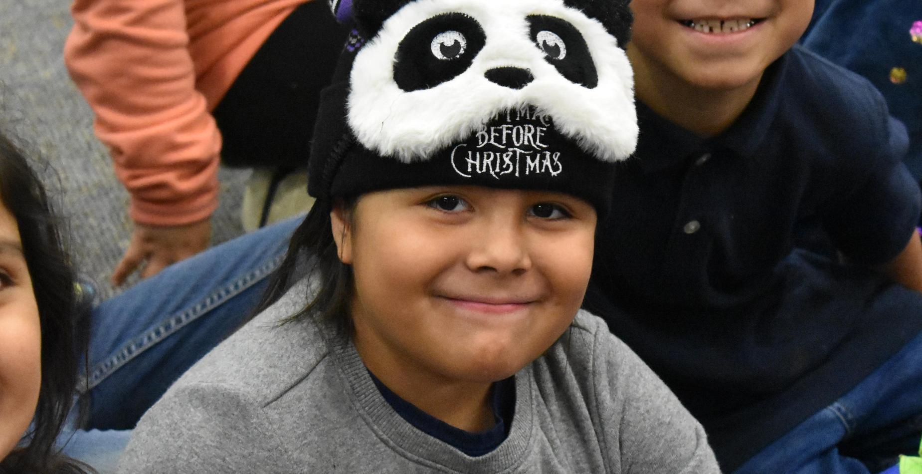 a little girl wearing a panda hat