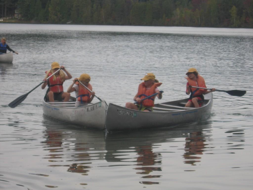 kids rowing boat on lake