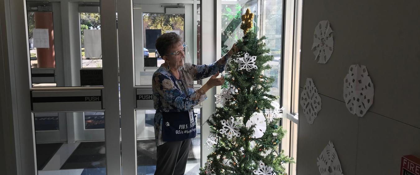 Smiga putting snowflakes on tree