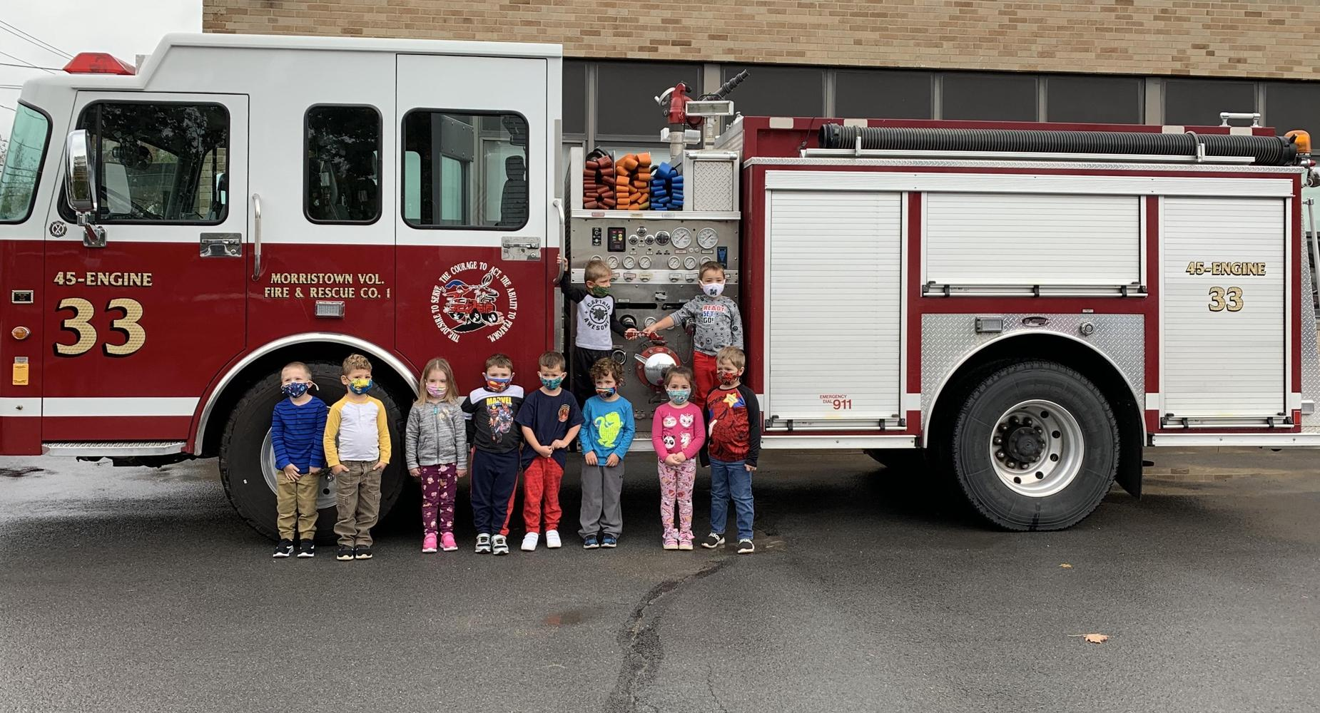 Elementary students standing with a fire truck.