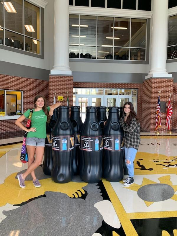 Incoming Recycling Club President, Bryce Back, and recent graduate Raquel Goddard pose with the new bins.
