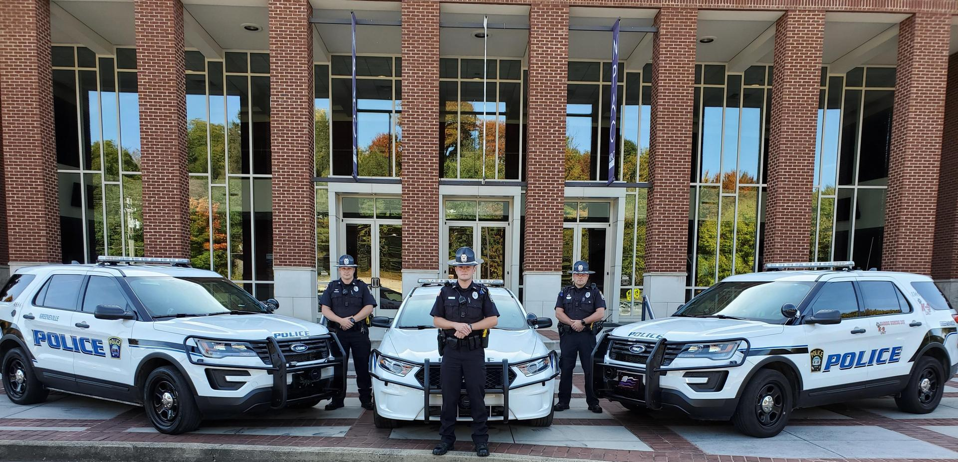(Pictures of three Greeneville Police units and three officers. A white Ford Taurus with blue lettering  and Two white Ford Explorer with blue lettering.