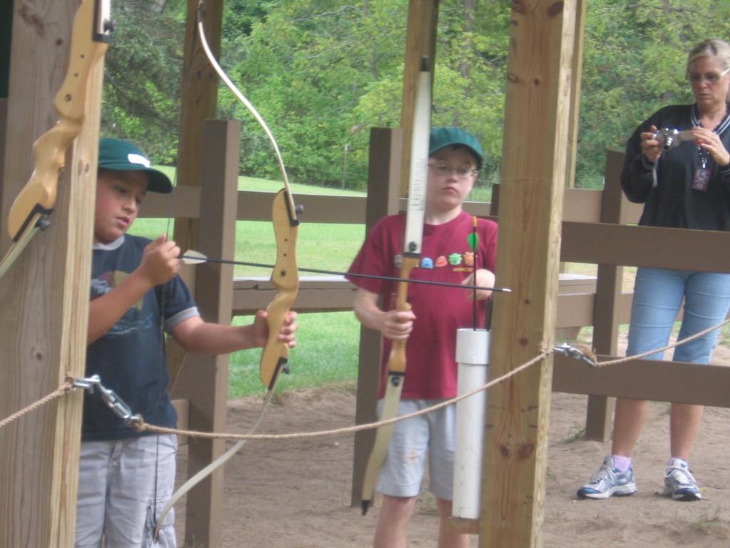 boys shoot arrow at camp