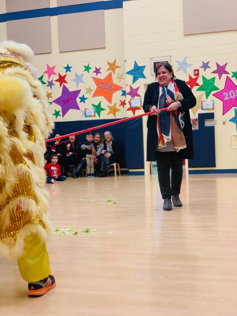 principal Birne touching the dragon with a large red pole