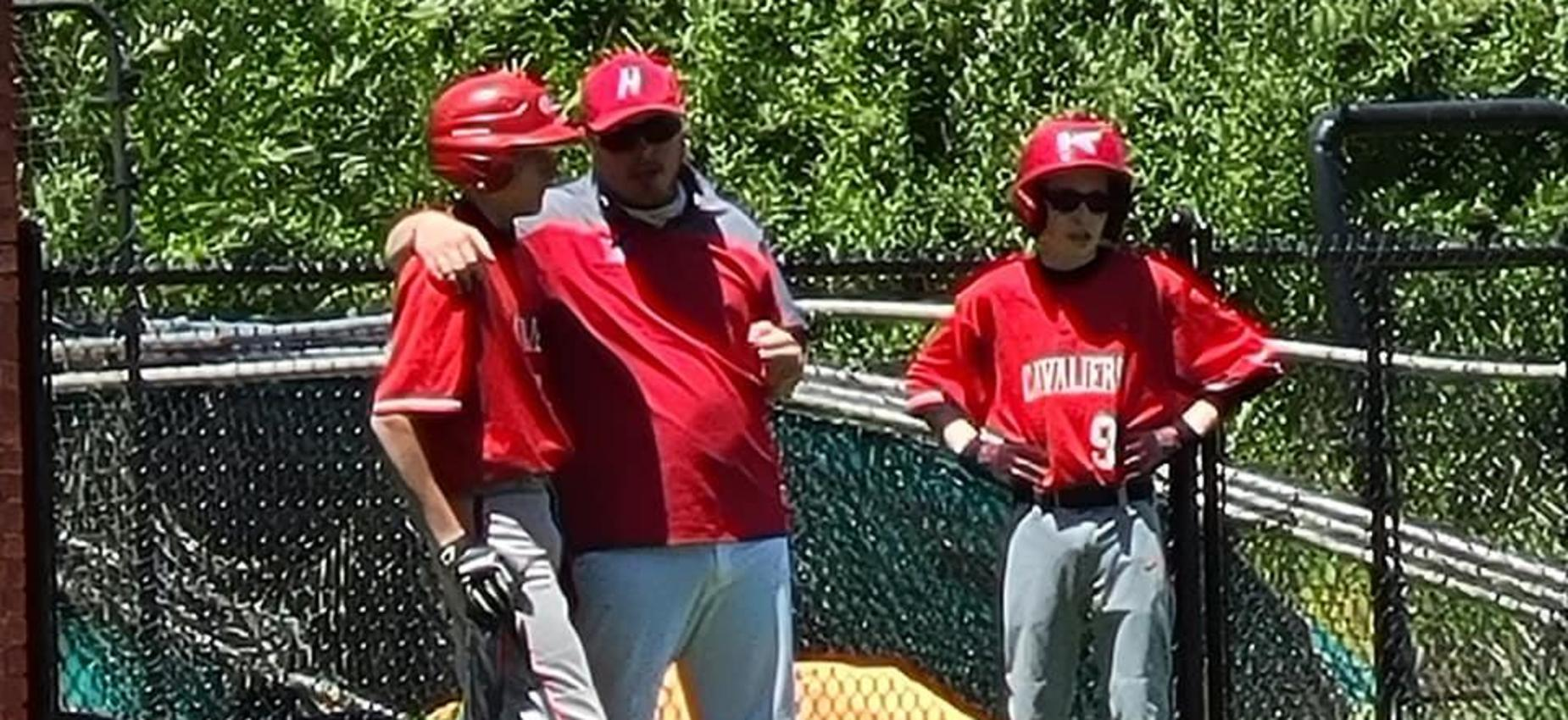 A coach talks to two baseball players during a game.