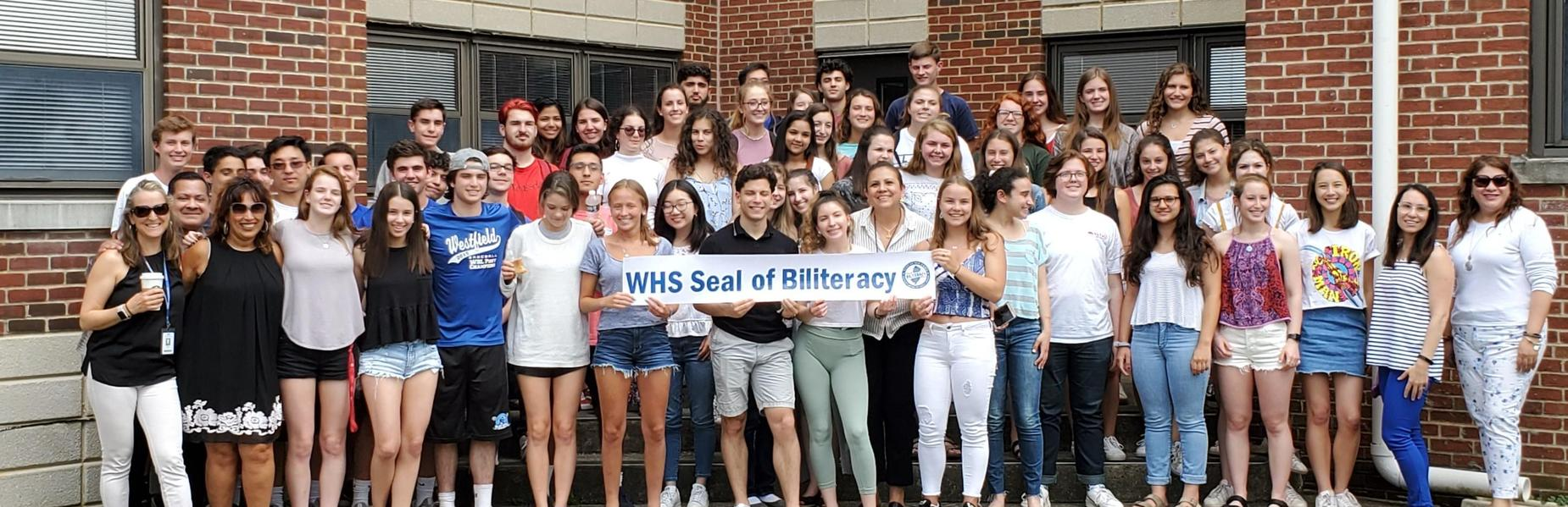 Photo of 90 students who attained the Seal of Biliteracy, pictured here with their instructors.