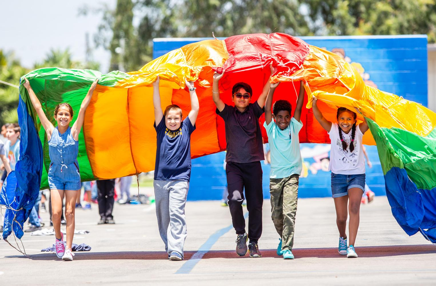 students carrying a parachute