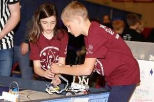 boy and girl in maroon shirt work on robot on a table