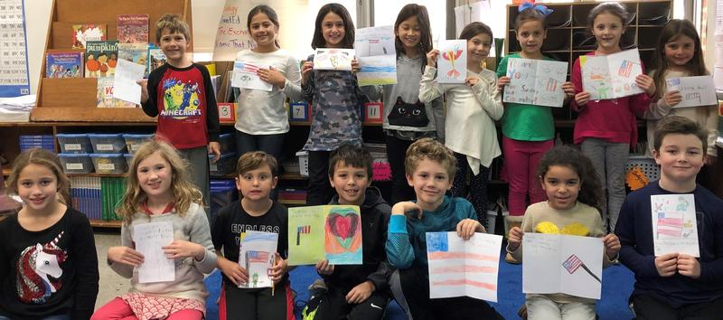 Washington School 2nd graders pose with cards and letters they created to send to troops overseas.