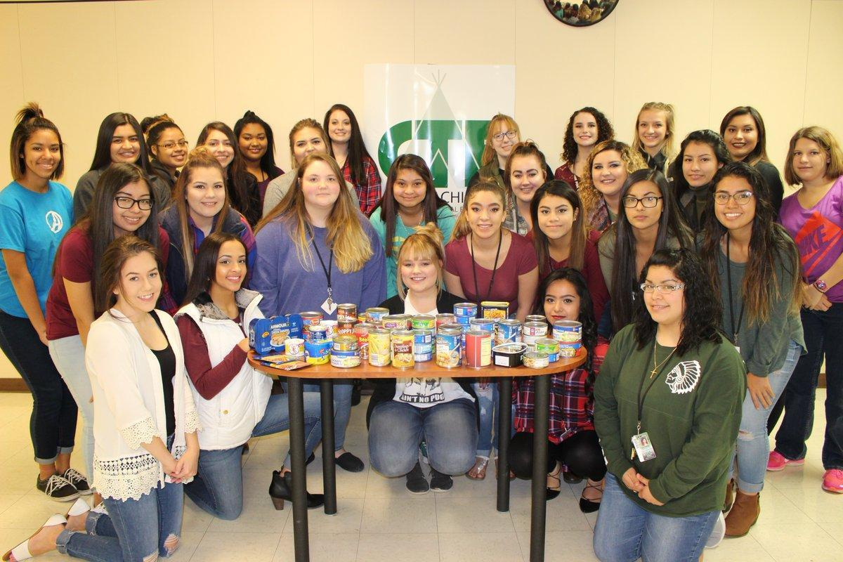 large group of students pose with canned food