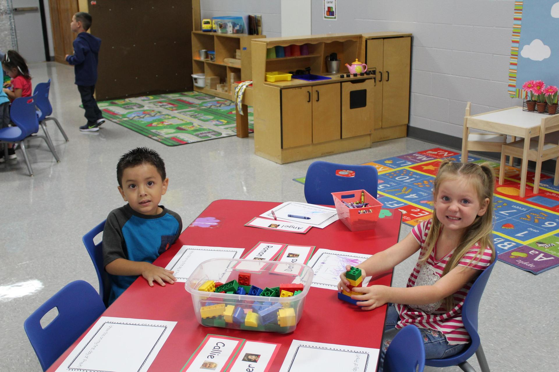 Pre-K students coloring at their desk