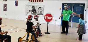 Picture of students on bicycles with helmets, and the teacher by a stop sign
